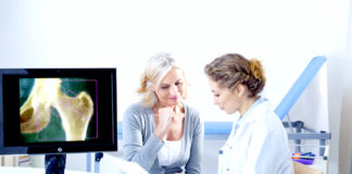 Doctor and patient reviewing x-ray, both female